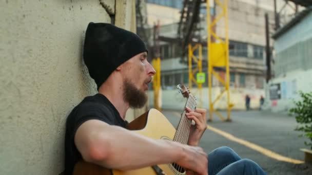 Bezdomovec na ulici, co sedí u plotu, dostává nějaké peníze hraním na kytaru. rozbili člověka, dostali se do chudoby, bídy, propustili ho, vyhodili, vyhodili. sociální problémy, koncepce nezaměstnanosti