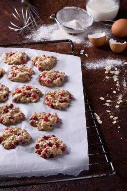Cranberry cookies on a baking tray, cooking ingredients over rustic kitchen table. Crispy appetizers.