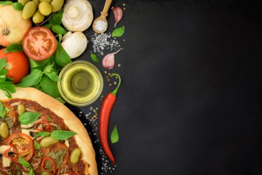 Hot Pizza with ingredients on black background with copy space.