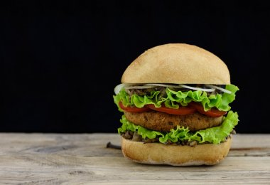 Fresh burger with falafel and salad on wood with black backdrop and copyspace.