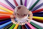 Skleněné zeměkoule a barevné tužky izolované na bílém