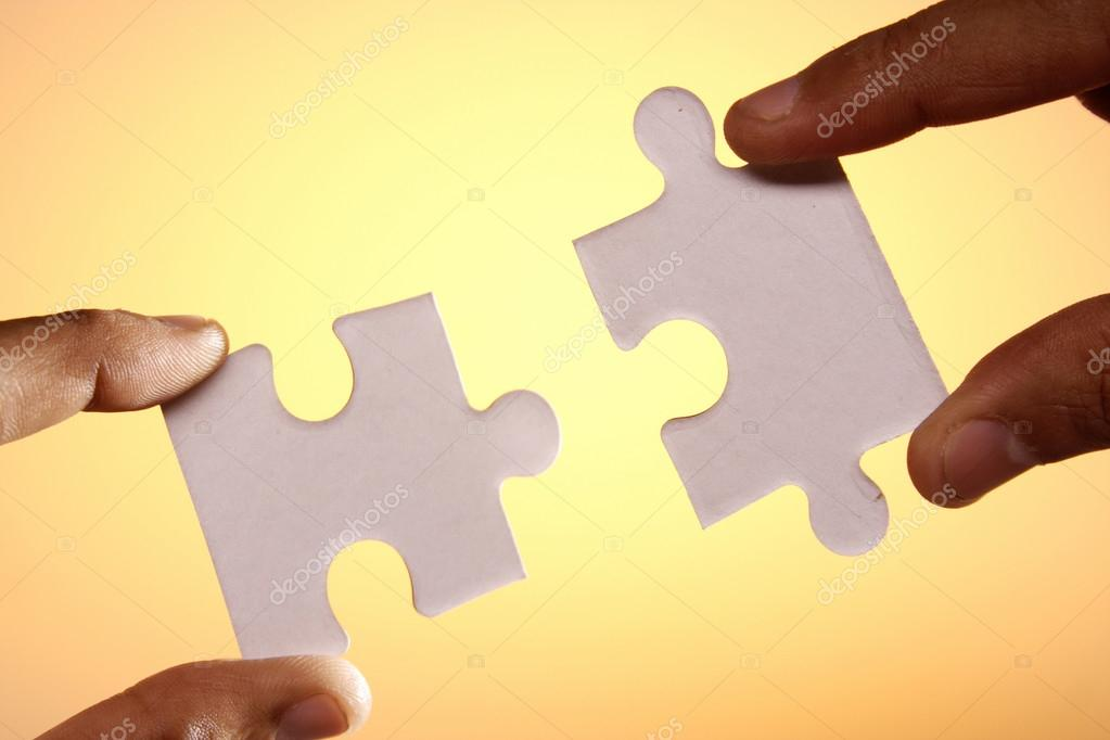 hands connecting two jigsaw puzzle pieces stock photo infocuss