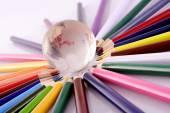 Elszigetelt fehér üveg globe és színes ceruzák