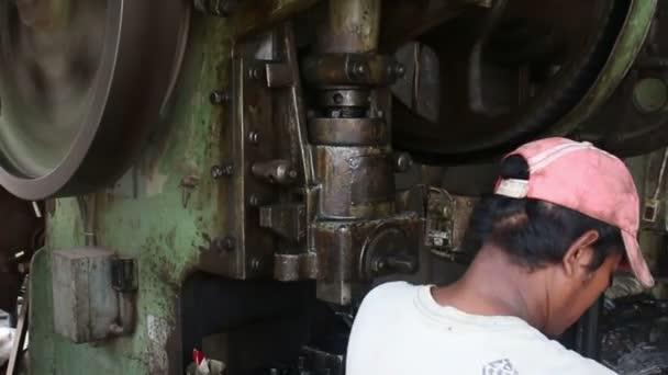 battambang, Kambodscha - 3. April 2016: Metallbearbeitungsmaschinenwerkstatt - höhere Winkel mcu der Stanzmaschine und Arbeiter
