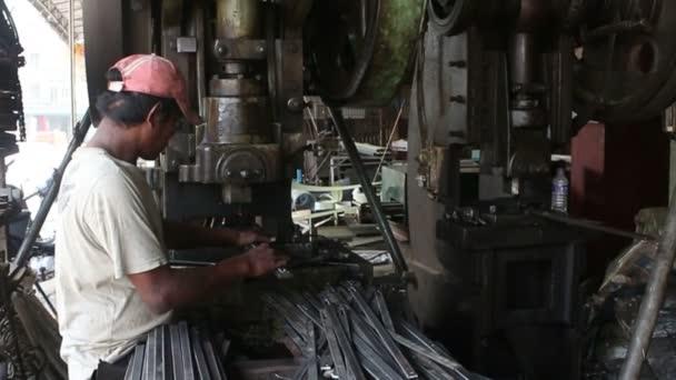 battambang, Kambodscha - 3. April 2016: Metallbearbeitungsmaschinenfabrik - pov Schuss Metallstangen in Metallpresse platziert