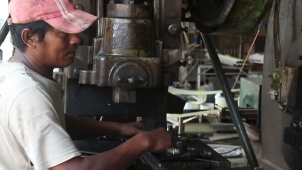 15. Mai 2016 - battambang, Kambodscha: Arbeiter aus mittlerer Großaufnahme füttert Metallpresse mit Rohlingen