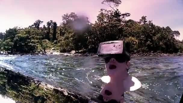 Man wearing VR virtual headset in ocean lagoon looks around in wonder