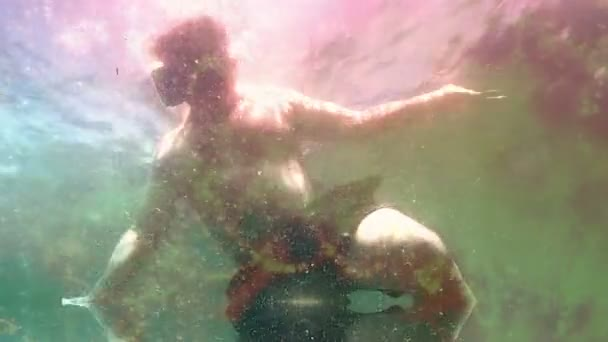 Medium shot Man descends under ocean waves wearing VR virtual reality headset
