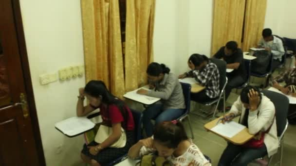 SIEM REAP, CAMBODIA - CIRCA APRIL 2016: Asian students taking a midterm exam with camera showing them from a high ang
