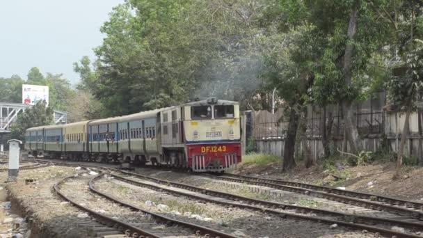 Yangon, Myanmar - 25. dubna 2014: Žluté a červené vlak dorazí a předá