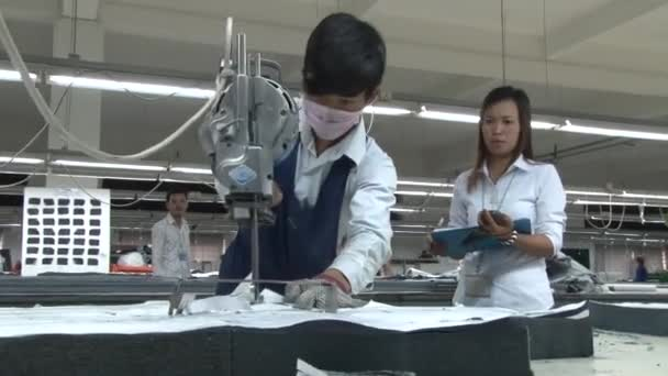 Asian Garment Industry Factory: Worker cuts with Supervisor Nearby
