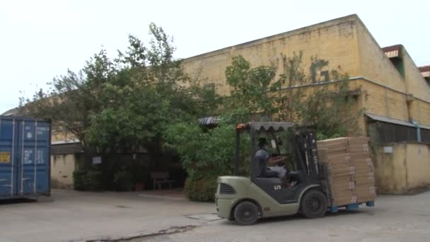 Asian Garment Industry Factory: WS EXT. forklift moving boxes in factory grounds