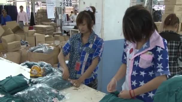 Textile Garment Factory: Workers pack completed garments into bags