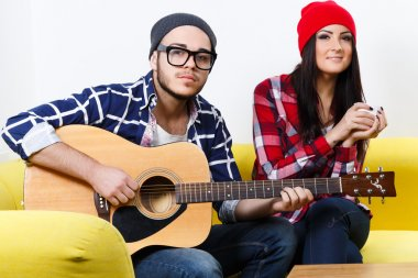 Boy and girl sitting with guitar