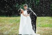 Fotografie Bräutigam und Braut im Regen stehen