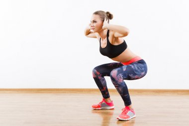 Sport fit girl doing physical exercises at gym