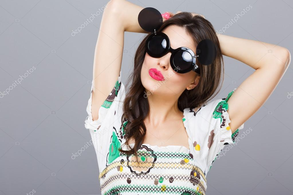 6e40e95ab2a Cheerful girl in black round sunglasses with side glasses. Looking at  camera