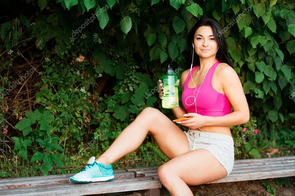 Pretty female athlete, resting on a bench after long workout
