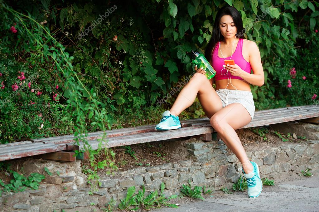 Fitness woman, resting on bench, holding bottle in her hand