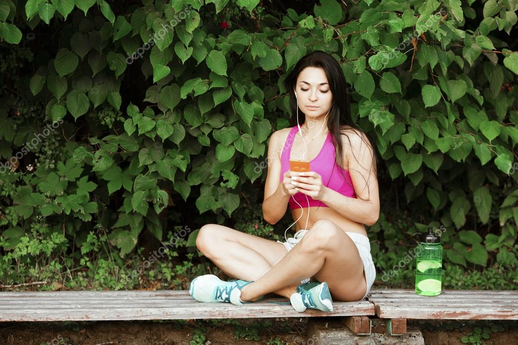 Brunette young woman, on bench after a long workout