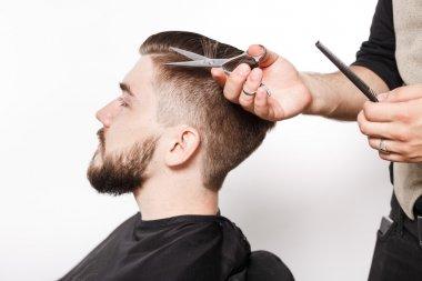 Hairdresser shaving young man