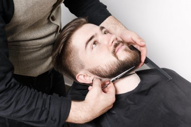 Hairdresser cutting beard