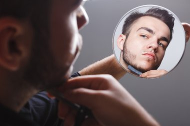 Bearded man shaving near the mirror