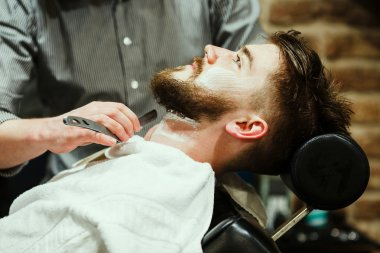 Barber shaving a bearded man