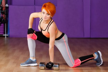 Young redhead girl in the gym