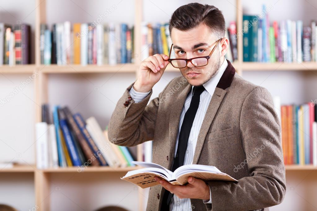 Man posing with a book in the office