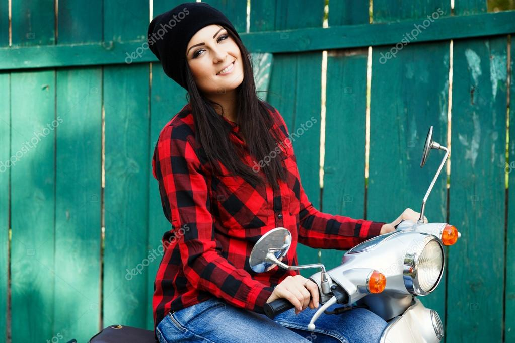 c2a4c4b7577b39 Smiling brunette woman, wearing in red and black plaid shirt, hat and  jeans, posing on vintage scooter and looking at camera, with green wooden  fence on a ...
