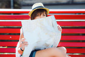 Fotografie tourist woman sitting on red bench