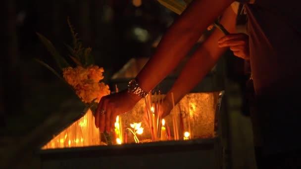 Buddha buddhista templom nap. Emberek meg a gyertyákat, virágokat és füstölők. Wat Nakha Ram, Phuket, Thaiföld. Lassú mozgás.
