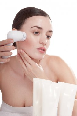 Woman with brush for deep cleansing facial