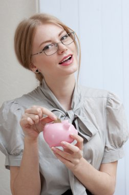 Happy smiling woman inserting coin in a piggy bank