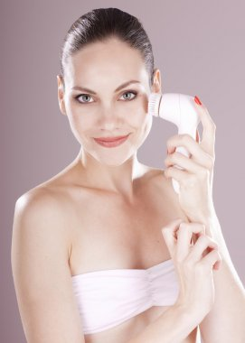 Charming woman with brush for deep cleansing facial