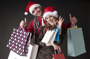 Happy young couple with shopping bags wearing Santa hat