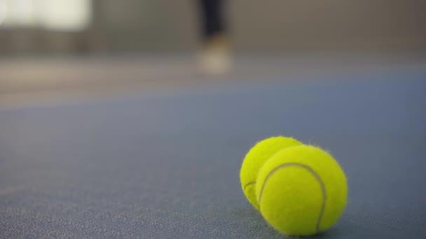 Detailní záběr žlutých tenisových míčků ležících na podlaze v tělocvičně s rozmazanou bělošskou sportovkyní sloužící v pozadí. Nerozpoznatelná žena školení na vnitřním kurtu před soutěží.