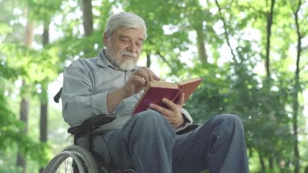 Spodní úhel pohledu na vstřebané postižené starší muž čtení knihy a usmívání. Inteligentní handicapovaný bělošský důchodce odpočívající s literaturou venku ve slunném letním parku.