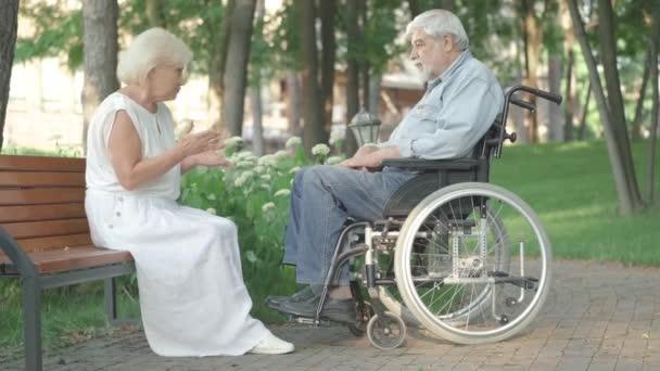 Široký záběr starší bělošky v bílých šatech sedící v letním parku na lavičce a mluvící se smutným paralyzovaným mužem na vozíčku. Manželka podporující paraplegický manžel po nehodě.