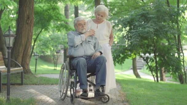 Široký záběr smutné krásné kavkazské starší ženy podporující invalidního muže sedícího na invalidním vozíku. Starý muž líbá ruku milující ženy. Paraplegik muž s manželem ve slunečném parku.