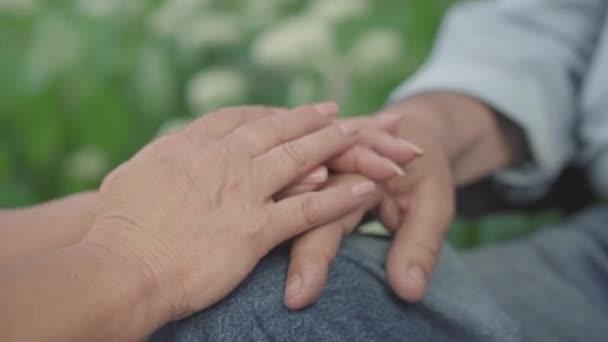 Großaufnahme alter männlicher und weiblicher Hände, die sich gegenseitig halten. Bis zur Unkenntlichkeit liebende Männer und Frauen, die ihren Ehepartner unterstützen. Konzept der ewigen Liebe und Einheit.
