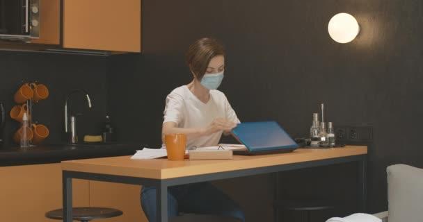Müde junge Geschäftsfrau schließt Laptop und zieht Covid-19 Gesichtsmaske aus. Porträt einer erschöpften kaukasischen Vorstandsvorsitzenden, die während der Coronavirus-Pandemie online arbeitet. Lebendiger Lebensstil.