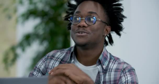 Close-up of confident African American man in eyeglasses talking in video chat online. Portrait of positive handsome young freelancer or businessman discussing strategy online. Cinema 4k ProRes HQ.