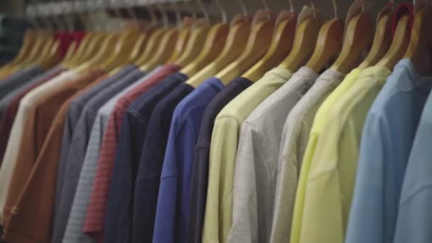 Row of multi-colored male T-shirts hanging on hanger in clothing shop. Clothes on rack in shopping mall.