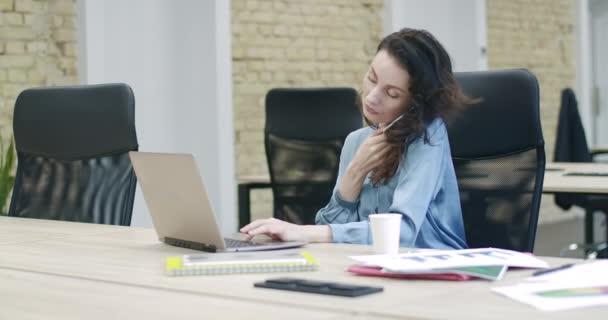 Young beautiful businesswoman talking on the phone and typing on laptop keyboard. Portrait of confident successful Caucasian woman working at the table in office. Cinema 4k ProRes HQ.