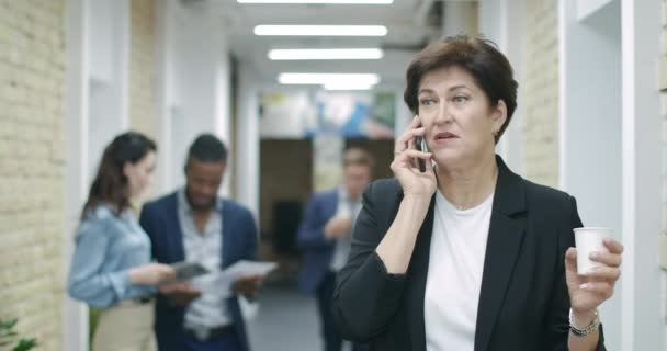 Beautiful mid-adult Caucasian woman with coffee cup talking on the phone with blurred multiracial colleagues or coworkers walking in office corridor at the background. Cinema 4k ProRes HQ.