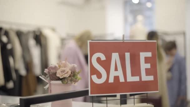 Detailní záběr oznámení o prodeji v obchodě s oblečením s rozmazanými ženskými nákupčími vybírajícími oblečení na pozadí. Bohaté bělošky nakupují v Černý pátek. Shopaholism koncept.