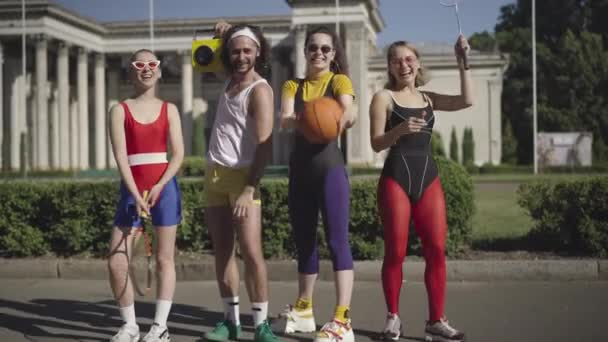 Wide shot portrait of smiling carefree man and women in 1980s style posing on sunny city street with vintage yellow tape recorder, basketball ball, and tennis racquets. Retro lifestyle concept.