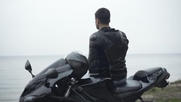 Zpětný pohled na sebevědomého středovýchodního motorkáře stojícího s motocyklem na břehu řeky a přemýšlejícího. Uvolněný mladý pohledný brunetka muž těší zatažený den venku. Koncept samoty.